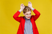 Funny business woman in red suit showing rabbit sign. Studio shot, isolated on yellow background