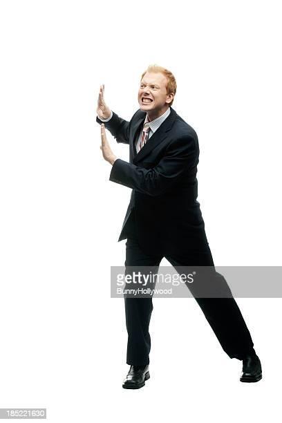 Lustiger Geschäftsmann hält eine Mauer auf Weiß