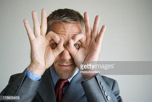Funny hombre de negocios mirando a través de las copas de los dedos de la mano