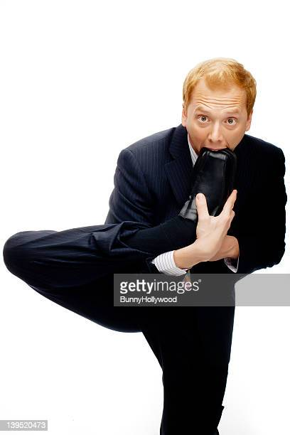 Funny businessman with foot in mouth on White