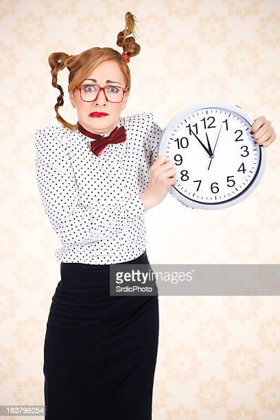 Funny businesswoman holding big clock and making funny face