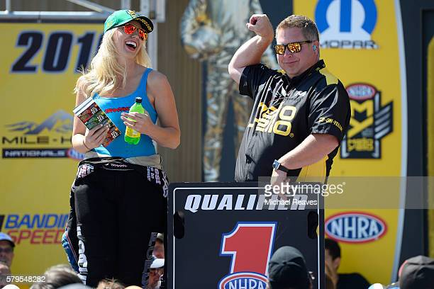 Funny Car driver Courtney Force laughs as NHRA trackside entertainment's Jason Logan flexes on stage during day three of the NHRA Mile High Nationals...