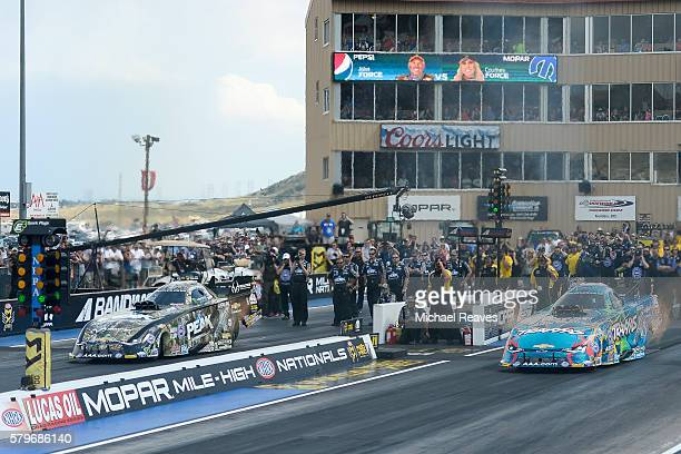 Funny Car drivers John Force and Courtney Force head down the track in the finals of day three of the NHRA Mile High Nationals at Bandimere Speedway...