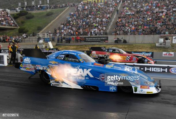 NHRA funny car drivers John Force left and his daughter Courtney Force race each other on the second day of the 38th annual NHRA Mopar Mile High...