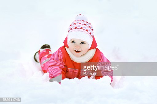 Engraçado criança a brincar com a neve no Inverno dia : Foto de stock
