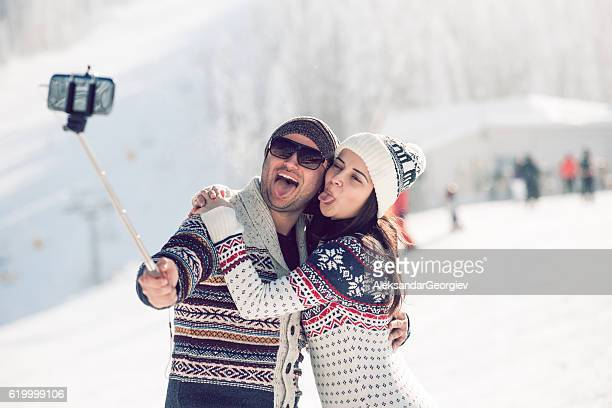 Funny Couple Taking Selfie on the Snow with Tongues out