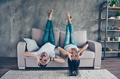 Funny couple with glasses gesturing is lying upside-down on the sofa at home. They are so cheerful, having fun together, go crazy, brother and sister