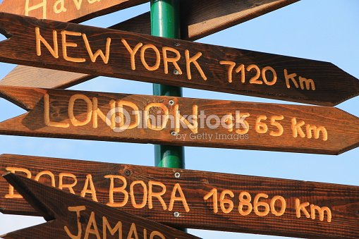 funny direction signpost with distance to many different cities