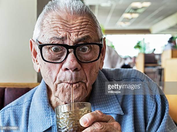 Divertente uomo anziano bere con paglia