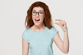 Funny excited redhead woman showing something very tiny little size by fingers, happy red-haired girl with open mouth amazed by small prices looking at camera isolated on white grey studio background