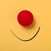 a red clown nose and a smile drawn on a yellow background