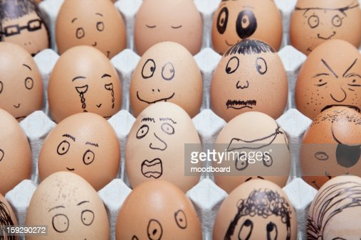 Funny faces on painted on brown eggs arranged in carton : Foto stock