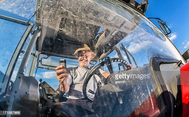 Funny farmer taking photos while driving tractor
