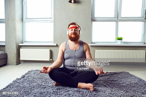A funny fat bearded man in the headphones does yoga : Foto de stock