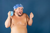 Funny fat man in blue cap and with sponge in the shower. Fun and cleanliness