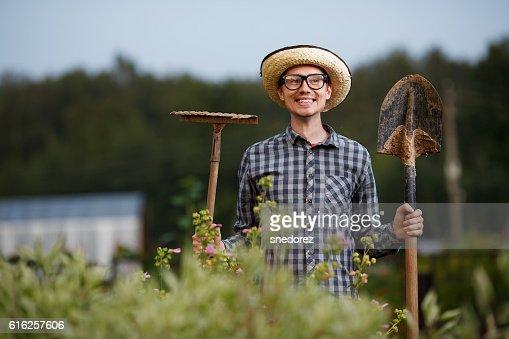 Funny gardener holding a shovel and rake outdoors : Foto de stock