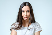 Funny girl sticking her tongue out isolated on white