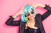 Funny girl with tongue stuck out wearing wig and sunglasses