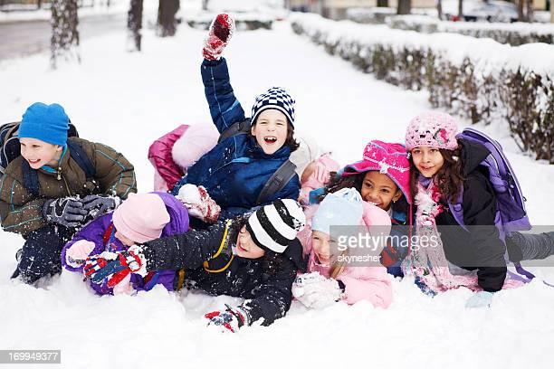 Lustiger Gruppe von Kindern im Schnee liegen.