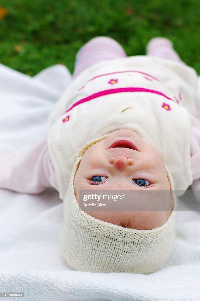 Funny happy upsidedown baby girl : Stock Photo