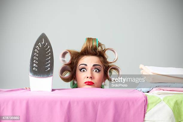 Funny housewife with curlers hiding behind ironing board