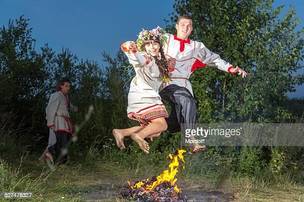 Lustiger springen über Holzfeuer im folk-Urlaub