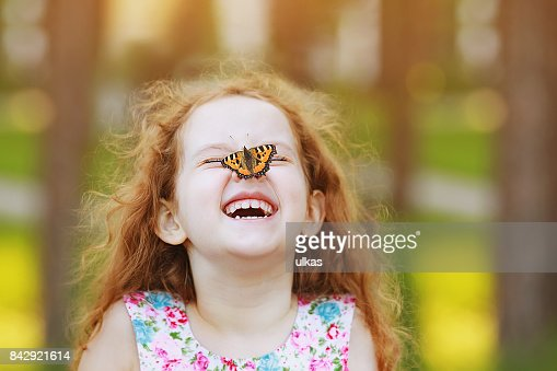 Funny laughing curly girl with a butterfly on his nose. : Foto stock
