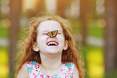 Funny laughing curly girl with a butterfly on his nose. Healthy smile with white teeth. Free breathing concept.