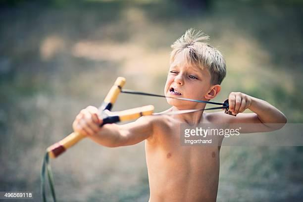 Funny little boy drawing a slingshot