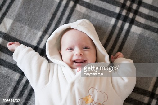 funny little girl lying on a gray plaid : Stock Photo