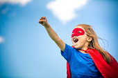 Funny little girl playing power super hero over blue sky background. Superhero concept.