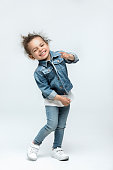 funny little kid girl in jeans isolated on white