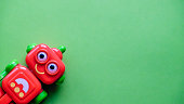 Smiling red toy robot on a green background