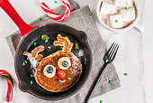 Funny food for Christmas. Kids breakfast pancake decorated like reindeer, with hot chocolate with marshmallow, white table copy space top view