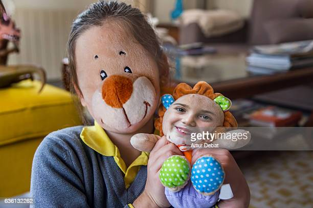 Funny picture swapping faces using smartphone application with little girl and her teddy toy.