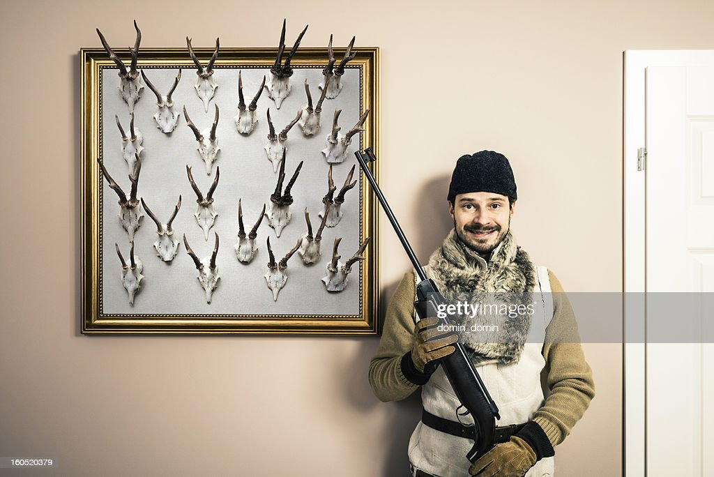 Funny portrait of hunter with shotgun and antlers, home interior