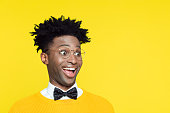 Funny portrait of surprised nerdy young afro American man wearing yellow sweater and black glasses, standing against yellow background.