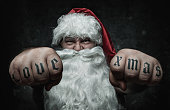 Funny Santa Claus showing fists with love xmas tattoo on them