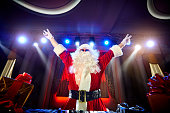 Funny Santa DJ mixes in the beams of light music for Christmas.
