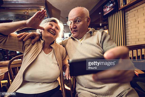 Funny senior couple taking a selfie with mobile phone.