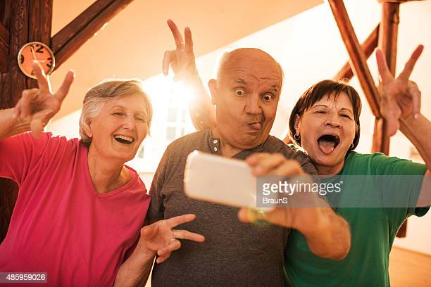 Funny senior friends taking a selfie with mobile phone.