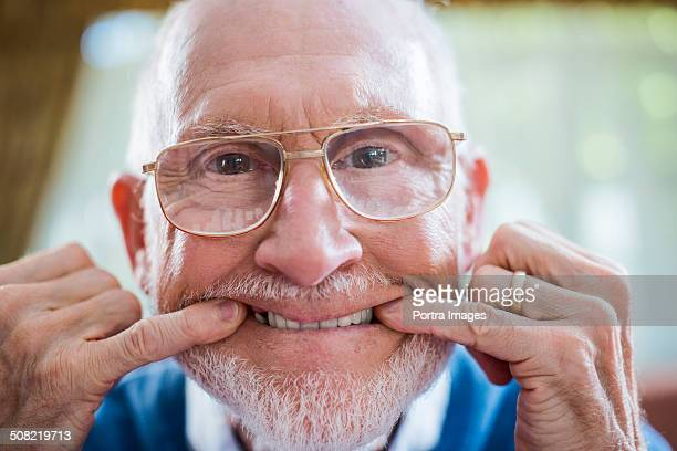 Funny senior man with fingers in mouth