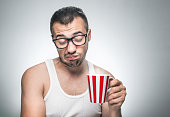 Displeased man with cup coffee. Nerd does not want to drink, isolated on gray background. Annoyed guy