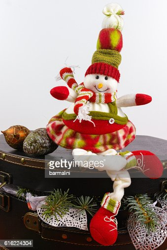 Funny snowman sits on vintage brouwn coffer with white christmas : Stock Photo