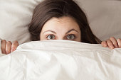 Funny surprised girl covering half of face with white blanket, young scared woman hiding and peeking from duvet, afraid of night monsters, feels embarrassed, wide awake, head shot close up, top view