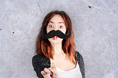 funny trendy fashion girl with paper mustache playing with emotion . Studio shot.