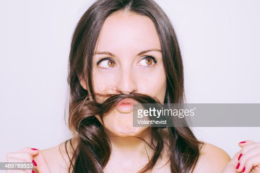 Funny woman portrait using hair like mustache