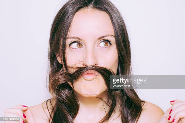 Funny woman portrait using hair like mustache