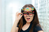 Happy girl wearing lots of colorful spectacles at the same time