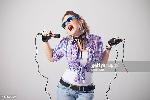Funny woman with sunglasses singing on microphone